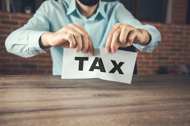 Homme d'affaires en colère déchirant une taxe au bureau