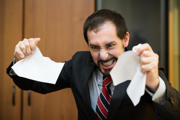 Homme d'affaires en colère déchire un document dans son bureau