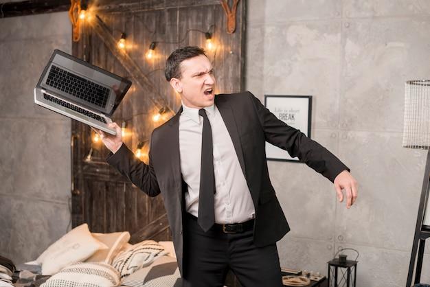 Homme d'affaires en colère sur le point de jeter un ordinateur portable