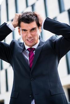 Homme d'affaires en colère se déchirer les cheveux dans le désespoir