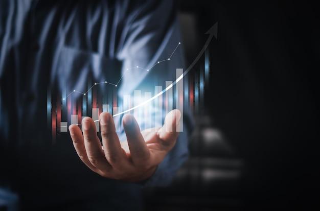Un homme d'affaires ou un commerçant montre un stock d'hologrammes virtuels en pleine croissance. , planification et stratégie, marché boursier, croissance de l'entreprise, concept de progrès ou de réussite. , investir dans le commerce.
