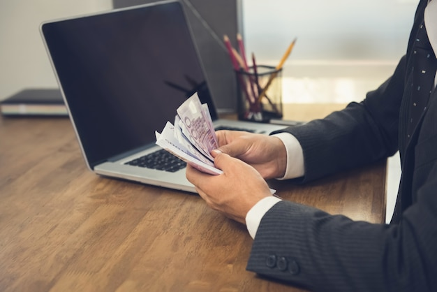 Homme d'affaires comptant de l'argent, des billets en euros, à son bureau