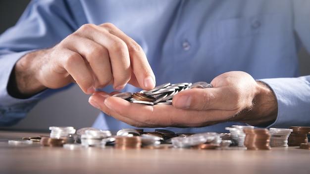Homme d'affaires comptant des pièces sur le bureau.
