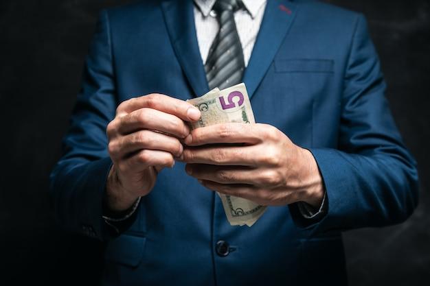 Homme d'affaires compte de l'argent sur une surface sombre