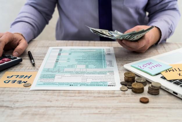 L'homme d'affaires compte des dollars et remplit un formulaire fiscal individuel us 1040. autocollant avec le temps d'imposition d'inscription. notion fiscale.