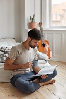 Homme d'affaires concentré aime le passe-temps de la littérature, repose avec un livre dans la chambre, est assis en posture de lotus sur le sol, tient la tasse