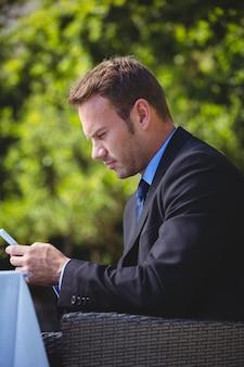Homme d'affaires concentré en regardant son smartphone