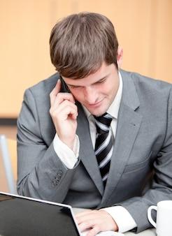 Homme d'affaires concentré utilisant son ordinateur portable tout en parlant au téléphone