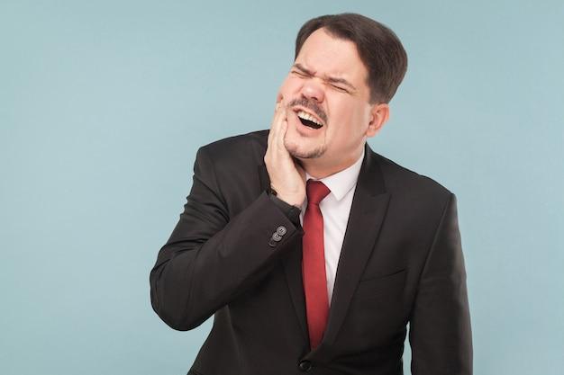 L'homme d'affaires de concept de mauvais sentiments a la douleur dentaire à pleines dents