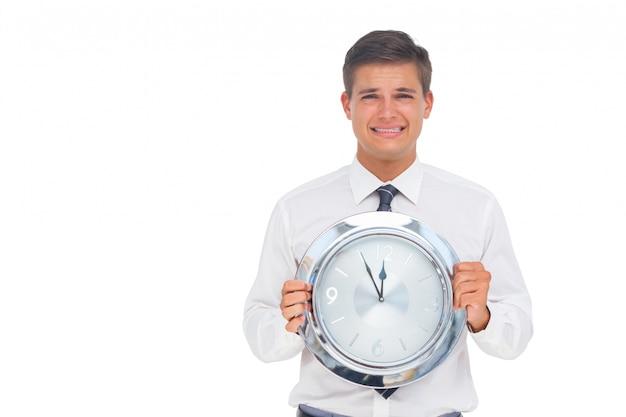 Homme d'affaires concerné tenant l'horloge