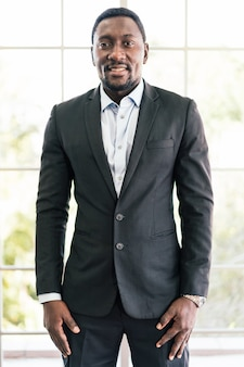 Homme d'affaires confiant afro-américain portant un costume regardant la caméra et souriant de bonne humeur