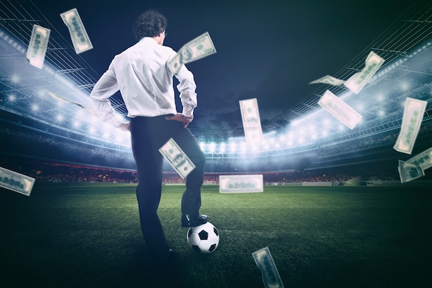 Homme d'affaires confiant au centre du terrain de football recueille beaucoup d'argent du football