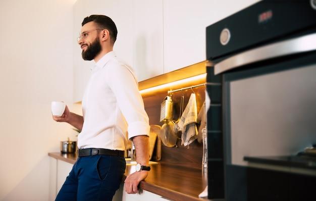 Homme D'affaires Confiant Barbu Détendu Dans Des Boissons De Vêtements Décontractés Intelligents Sent Le Café Et Réfléchi à La Cuisine Domestique Photo Premium