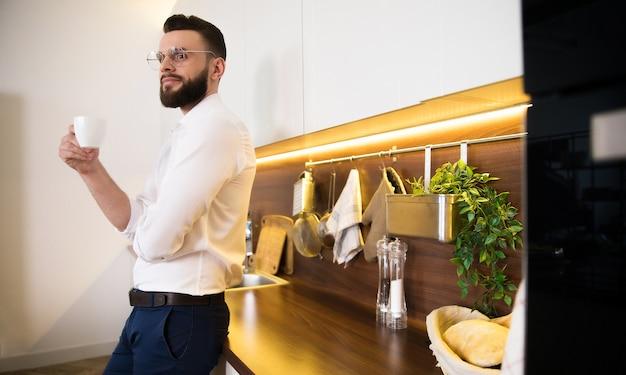 Homme d'affaires confiant barbu détendu dans des boissons de vêtements décontractés intelligents sent le café et réfléchi à la cuisine domestique