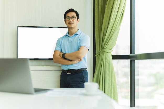 Homme d'affaires confiant avec les bras croisés contre l'écran dans un bureau