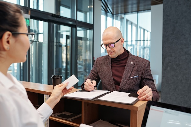 Homme d'affaires confiant chauve remplissant le formulaire par comptoir devant la réceptionniste en arrivant à l'hôtel