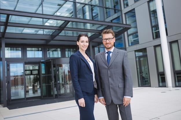 Homme d'affaires confiant avec un collègue debout à l'extérieur de l'immeuble de bureaux