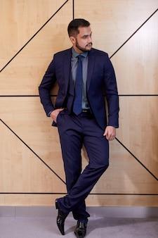 Homme d'affaires confiant en costume bleu élégant posant isolé dans la salle de conférence, se tenir debout à côté. concept de gens d & # 39; affaires