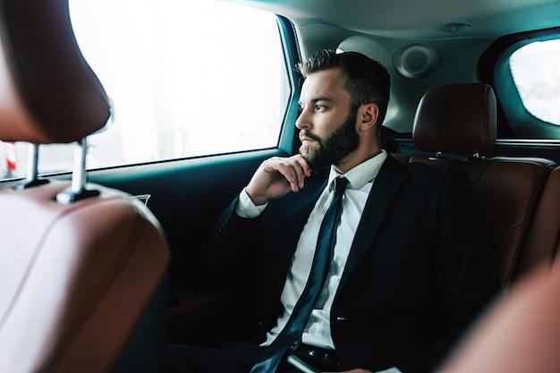 Homme d'affaires confiant et élégant en tenue de soirée assis dans la voiture de société ou le taxi