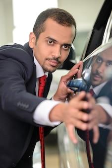 Homme d'affaires confiant examinant une voiture.