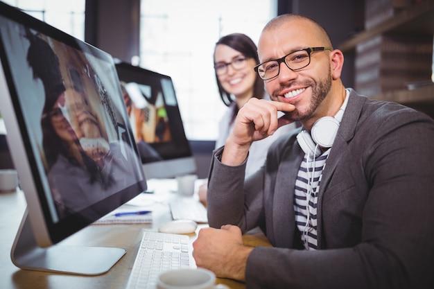 Homme d'affaires confiant par ordinateur avec collègue en arrière-plan
