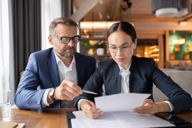 Homme d'affaires confiant pointant sur le contrat pendant que sa collègue lisant ses termes et points lors d'une réunion au restaurant