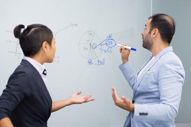 Homme d'affaires confiant, prendre des notes à bord pour une collègue