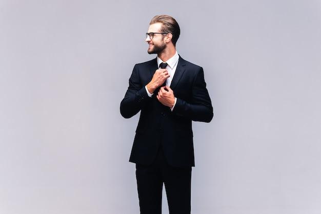 Homme d'affaires confiant. prise de vue en studio d'un beau jeune homme en costume complet ajustant sa cravate et souriant