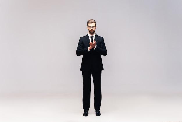 Homme d'affaires confiant. prise de vue en studio sur toute la longueur d'un beau jeune homme en costume complet gardant les mains jointes et regardant la caméra