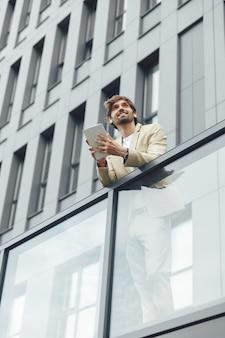 Homme d'affaires confiant souriant en tenue formelle à l'aide de tablette numérique pour le travail. vue d'angle faible