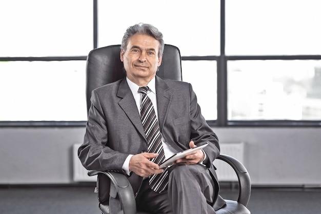 Homme d'affaires confiant avec tablette numérique assis au bureau .photo avec espace copie
