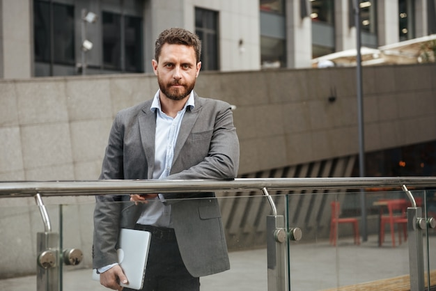 Homme d'affaires confiant en tenue de soirée tenant un ordinateur portable argenté fermé à la main, tout en se tenant devant un immeuble de bureaux en zone urbaine