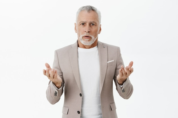 Homme d'affaires confus et inquiet en costume l'air perplexe, ne peut pas comprendre ce qui se passe