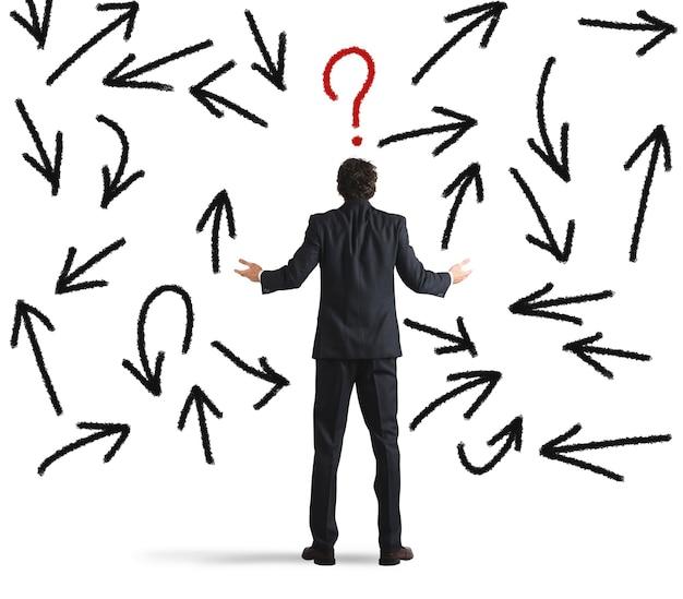 Homme d'affaires confus à la recherche d'un mur avec des flèches directionnelles