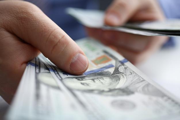 L'homme d'affaires considère les dollars en espèces au bureau