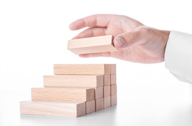 Homme d'affaires construit une échelle à partir de blocs de bois