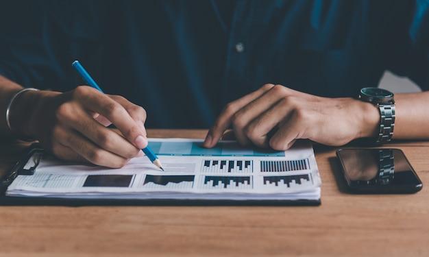 Homme d'affaires consultez le graphique et en examinant les données des bénéfices de l'entreprise remplis de docu