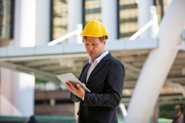 Homme affaires, ou, contremaître, casque, regarder, plan, contre, bâtiment