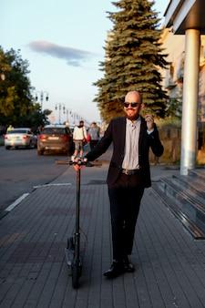 Homme affaires, conversation téléphone, côté, scooter électrique