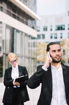 Homme affaires, conversation téléphone portable, et, femme affaires, écrire, presse-papiers, dans, les, fond