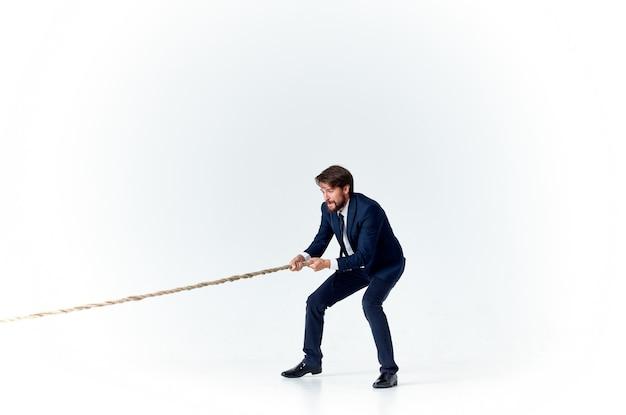 Homme d'affaires avec une corde dans son modèle de tension des mains d'atteindre l'objectif