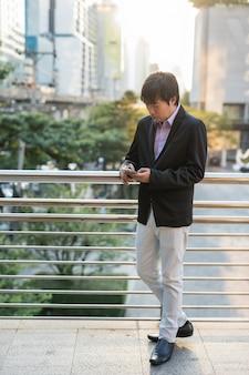 Homme d'affaires coréen à l'aide de smartphone en ville