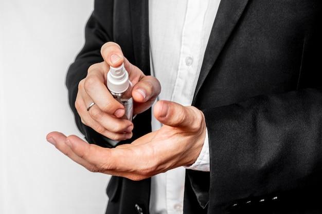 Un homme d'affaires en costume d'affaires vaporise des antiseptiques à l'alcool à partir d'un vaporisateur sur sa main