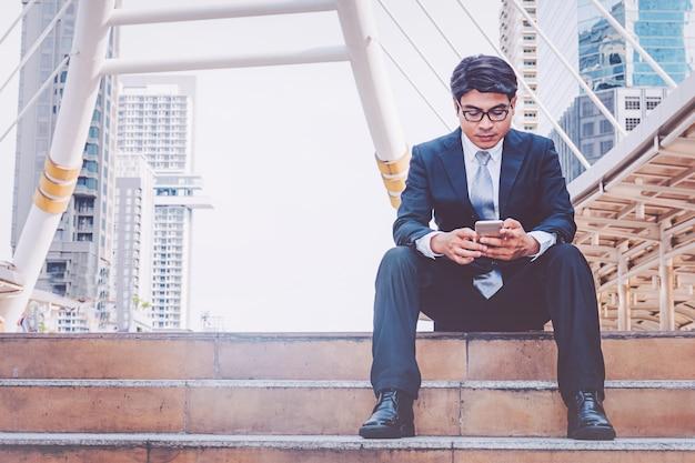 Homme d'affaires en costume à l'aide de smartphone à la ville
