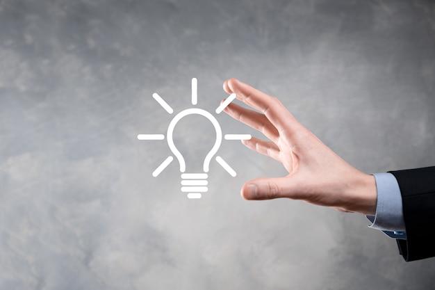 Homme d'affaires en costume avec une ampoule dans ses mains. tient une icône idée rougeoyante dans sa main. avec une place pour le texte.