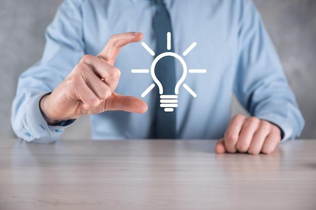 Homme d'affaires en costume avec une ampoule dans ses mains. tient une icône idée rougeoyante dans sa main.