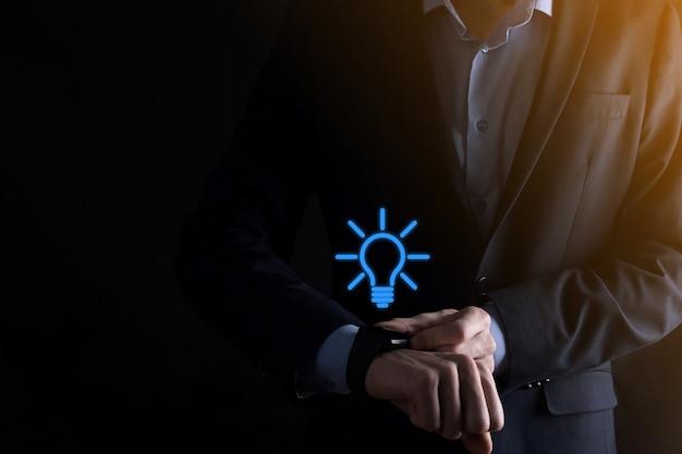 Homme d'affaires en costume avec une ampoule dans ses mains.