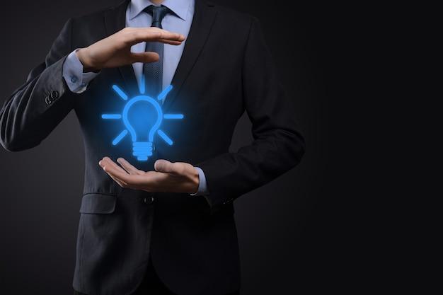 Homme d'affaires en costume avec une ampoule dans ses mains