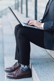 Homme d'affaires en costume assis sur les marches et travaillant sur un ordinateur portable.