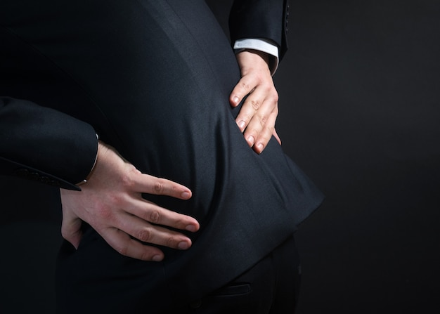 Homme d'affaires en costume ayant un mal de dos
